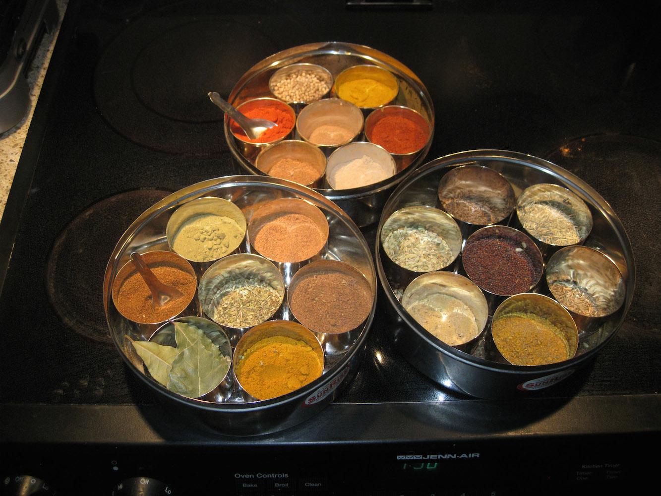 A picture of three round containers, each of which contains seven round containers filled with spices.