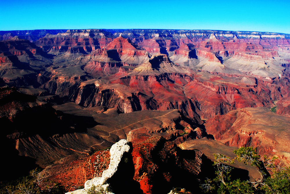 An image of the Grand Canyon. The formations of rock reveal colored patterns at different layers.