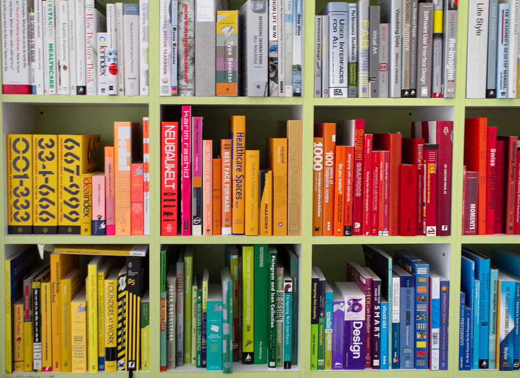 Books, arranged by color, on shelves.