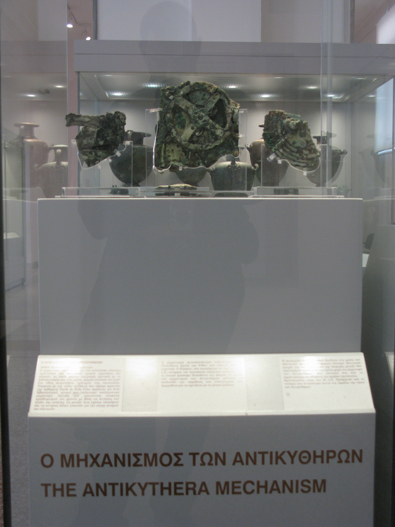 Photo of The Antikythera Mechanism exhibit at the National Archeological Museum of Athens. Grecian urns are on display in the background.