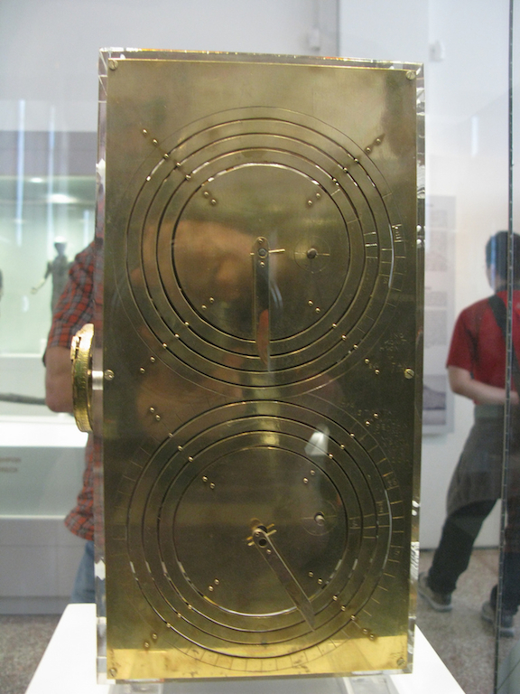 Photo of a display case containing a metallic object with two sets of concentric circles inscribed on its face, and dials akin to those of an analog clock or watch. Museums patrons in background.