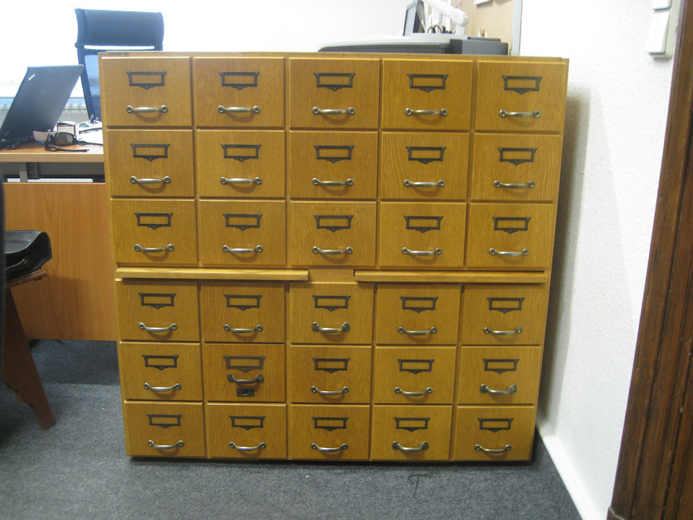 Photo of a wooden card catalog cabinet. Six drawers high; five drawers wide; two drawers extendable from mid-cabinet. The material appears to be oak.