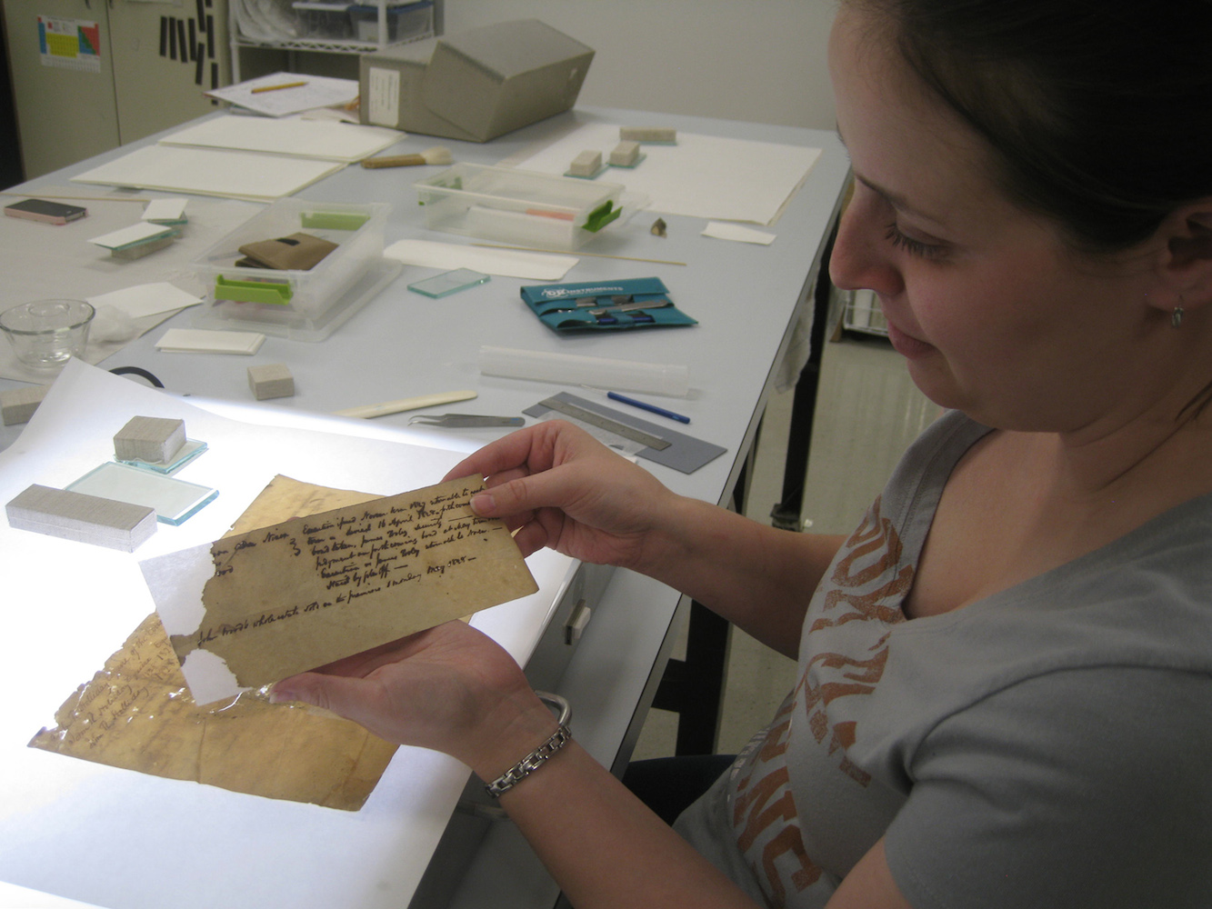 An archivist works at preserving an old text.