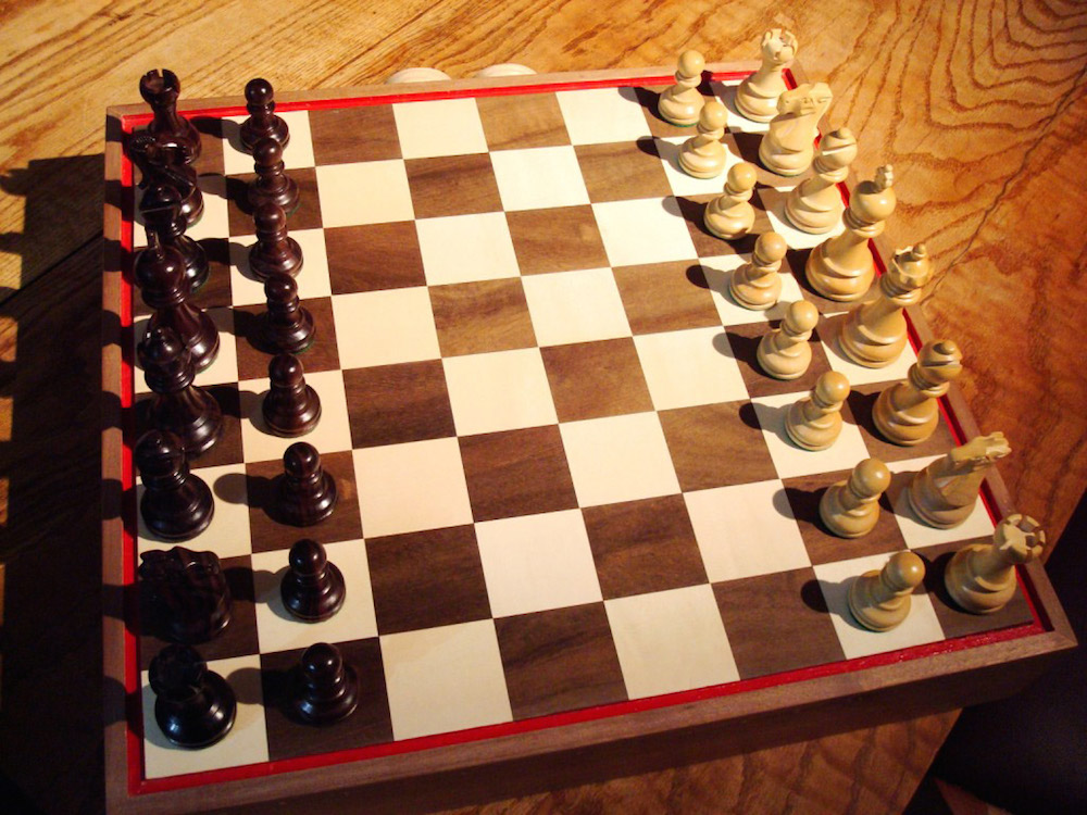 A chess set in black and white; a chess board with a full complement of thirty-two pieces; sixteen white and sixteen black pieces; a king and a queen, two bishops, two knights, two castles and eight pawns, each in black and in white.