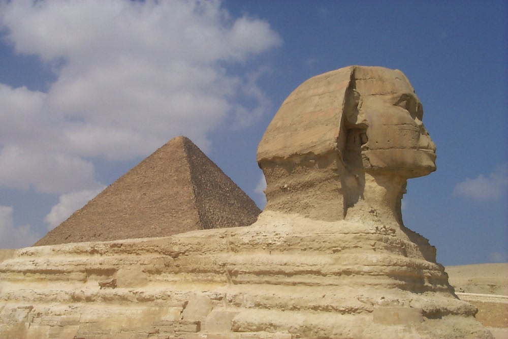 Image of The Great Sphinx at Giza with upper half of the Great Pyramid in the background. The surface of the Sphinx appears well worn by the ravages of time. The image is evocative of ancient Egypt.