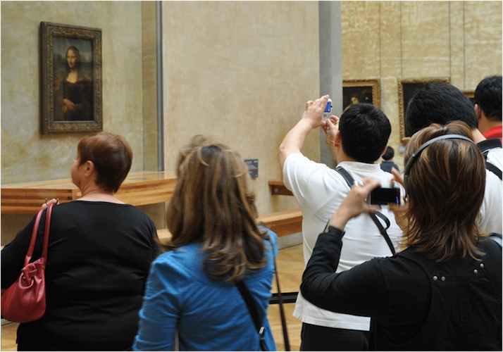 "Image depicts several people standing and looking at museum displays. La Joconde (aka ""The Mona Lisa"") appears on a wall in the background."