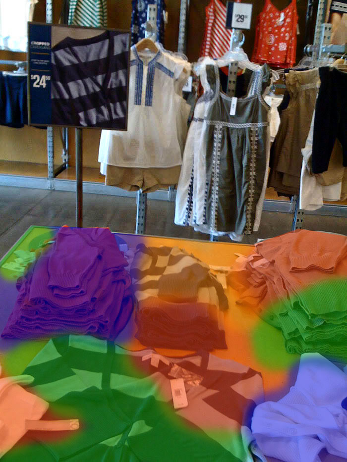 Overhead view of a clothing store. A table covered with merchandize is highlighted with a multicolored overlay that tints various items in red, green, orange, and blue.